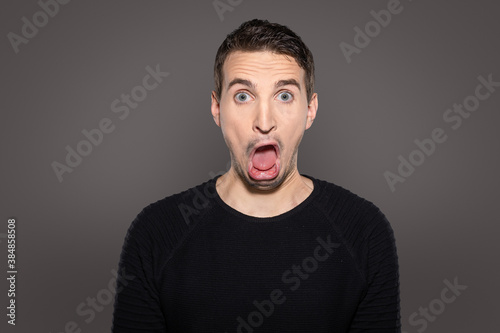 grotesque face with open mouth of an adult man isolated on grey background Wallpaper Mural