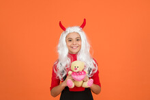 Shopping In Toy Shop. Carnival Costume Party. Trick Or Treat. Celebrate The Holidays. Childhood. Happy Halloween Devil Girl. Teenage Child In Imp Horns. Cheerful Kid Hold Teddy Bear Toy