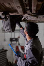 Young Caucasian Auto Mechanic In Uniform Is Examining Car Wheels In Auto Service. Male Is Concentrated On Work