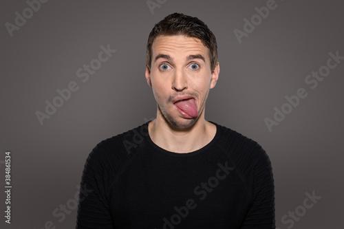 crazy smiling man having fun while show his tongue and having a grotesque face w Canvas Print
