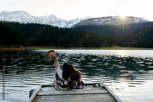 Fotomural Carefree lesbian couple sitting by an alpine lake