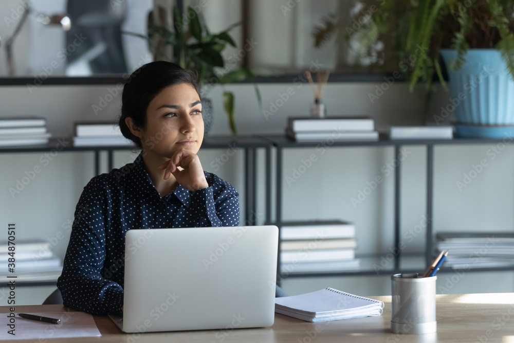 Fototapeta Thoughtful young indian businesswoman sit at desk distracted from computer work look in distance thinking. Pensive ethnic female employee make plan or decision in office. Business vision concept.
