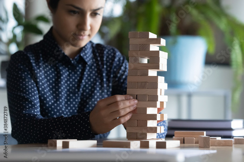 Close up of concentrated smart young Indian woman sit at desk in office brainstorm play wooden stack game alone Poster Mural XXL