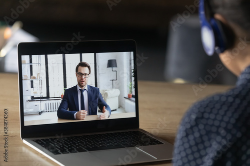Fototapeta Back close up view of employee in headphones have video call with employer on laptop in office