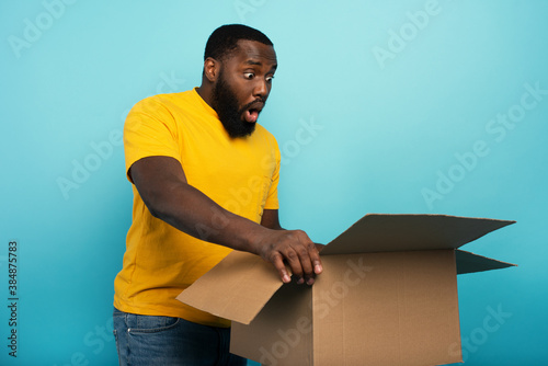 Obraz Happy boy receives a package from online shop order. happy and surprised expression. Blue background. - fototapety do salonu