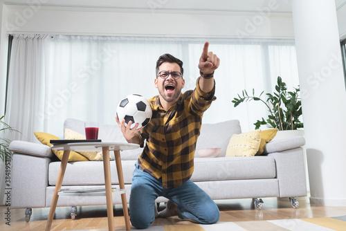 Fototapeta Football fan celebrating victory at home obraz