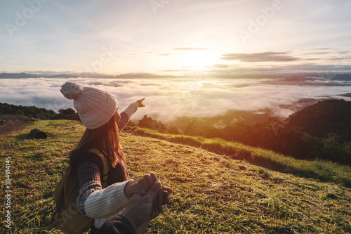 Obraz Young couple travelers looking at the sunrise and the sea of mist on the mountain in the morning, Travel lifestyle concept - fototapety do salonu