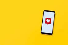 Top View Of Cell Phone With Heart Emoticon. White Screen And Yellow Background, Copy Space. Social Network Concept.