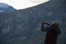 A Man Holds A Shotgun Downrang...