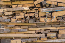 Stacked As A Woodpile Are Many Wooden Yellow Gray Boards, Planks, And Slats Of Various Sizes And Cross-sections.