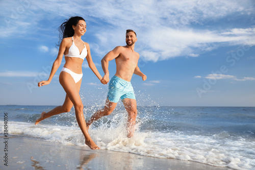 Obraz Happy young couple running together on beach - fototapety do salonu