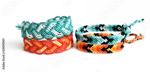 Selective focus of 4 woven DIY friendship bracelets handmade of embroidery bright thread with knots isolated on white background Fototapeta