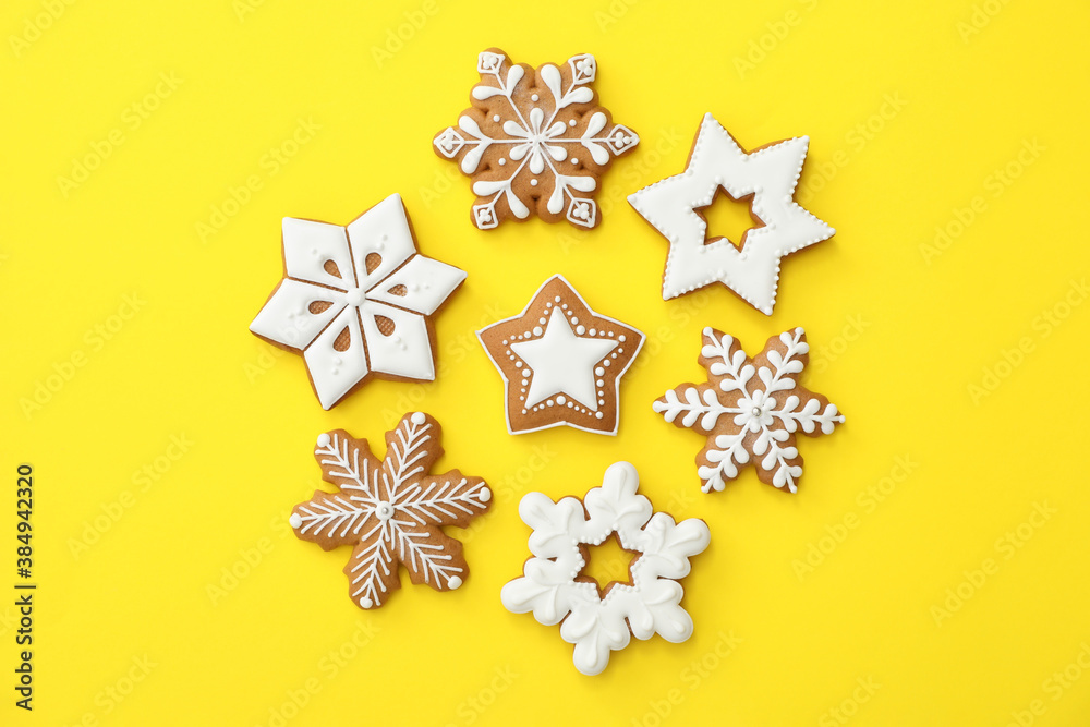 Fototapeta Christmas snowflake shaped gingerbread cookies on yellow background, flat lay
