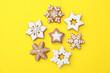 Leinwandbild Motiv Christmas snowflake shaped gingerbread cookies on yellow background, flat lay