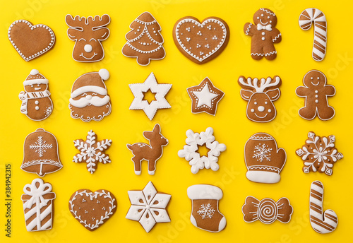 Obraz Different Christmas gingerbread cookies on yellow background, flat lay - fototapety do salonu