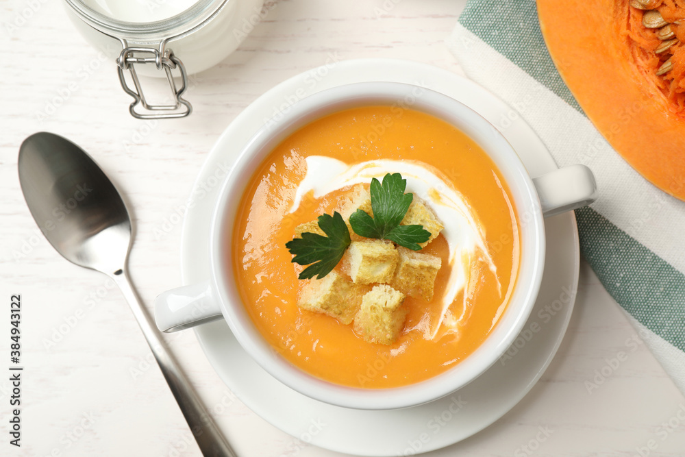 Fototapeta Delicious pumpkin soup in bowl served on white wooden table, flat lay