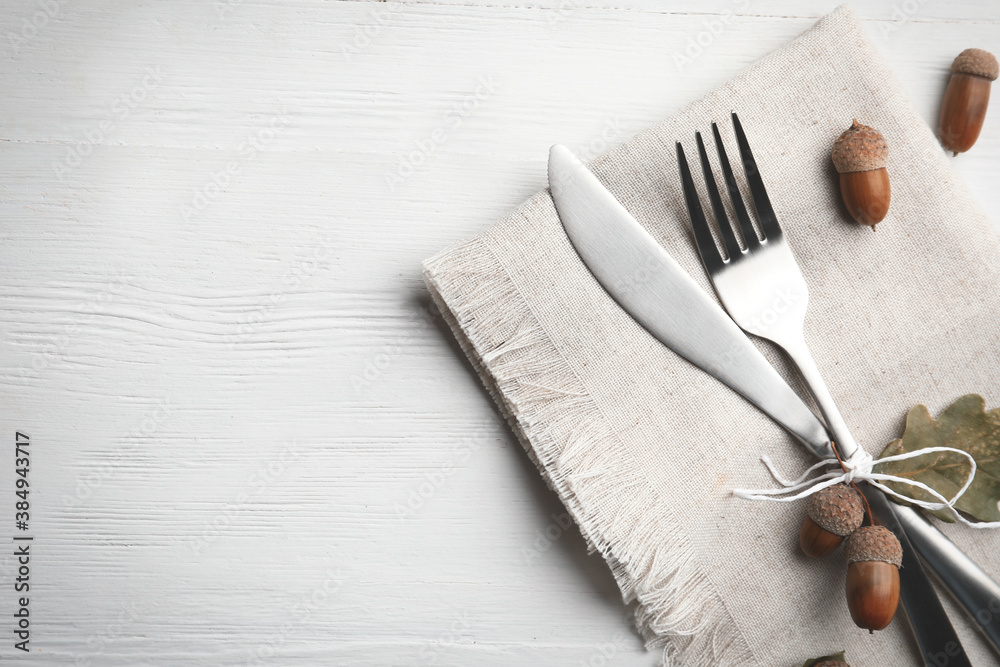 Fototapeta Cutlery, acorns and napkin on white wooden background, flat lay with space for text. Table setting elements