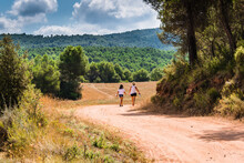 Mother With Her Daughter Walking Through Nature Along A Forest Path In Anoia, Barcelona