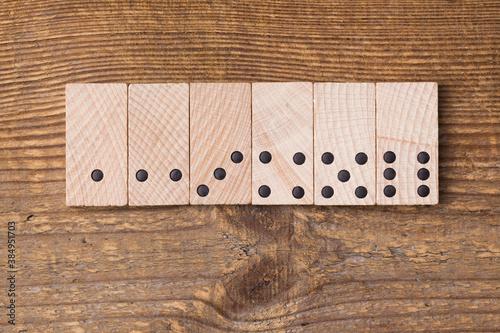 Drewniane klocki domina, leżące na starej desce, ciąg cyfr.