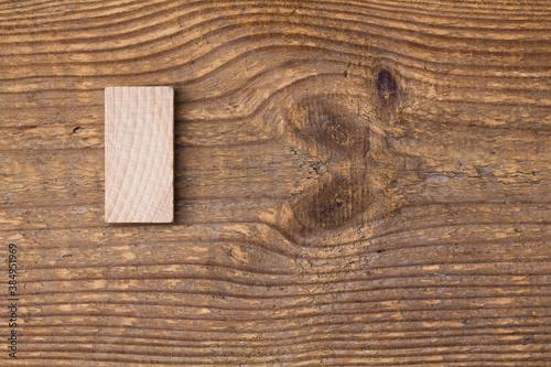 Obraz Pusty, drewniany klocek domina, leżący na starej desce. - fototapety do salonu