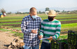 Hispanic farmer in protective face mask discussing work plan with his partner on farm field. Pandemic prevention and social distancing concept