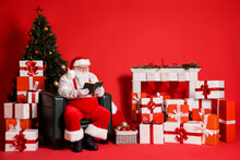 Portrait Of His He Attractive Fat Overweight Focused Concentrated Wise Santa Father Sitting In Armchair Reading Book Spending Festal Day Isolated Bright Vivid Shine Vibrant Red Color Background