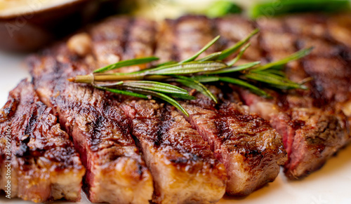 Fototapeta Close up view on serving of marinated grilled rib eye steak with baked potatoes and vegetables