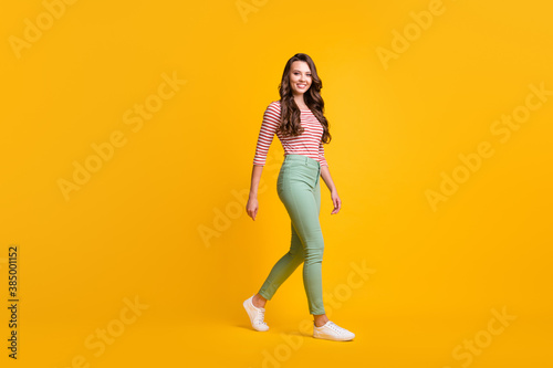 Full length body size side profile photo of girl with curly hair hurrying up smiling isolated on vivid yellow color background