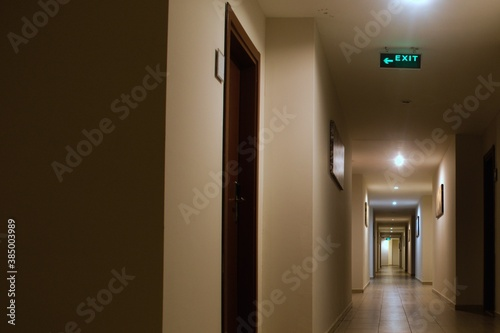 Fototapeta long interior corridor with many doors and exit signs