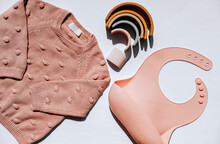 Set For Girls, Pink Sweater, Silicone Bib And Toy Rainbow. High Quality Photo