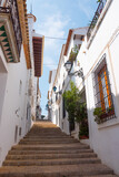 Fototapeta Fototapety na drzwi - Beautiful narrow street in Altea, Costa Blanca, Valencian Community, Spain. Historical center/old town. Stone stairs going up. Vertical shot. Typical ancient architecture.
