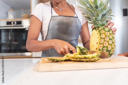 Fototapeta Woman chopping pineapple slices in kitchen obraz