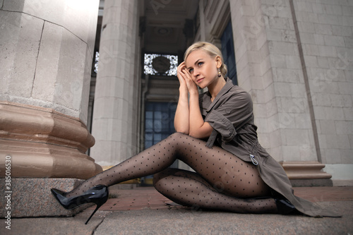 Beautiful blonde woman with perfect legs in pantyhose posing outdoor at the autumn street in the lights of the setting sun Canvas-taulu