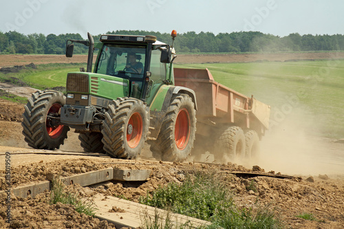 Fotomural A tractor with empty tipper trailer drives up a dike on a dusty track; in the background a green polder and a reenforced dike with a new layer of clay