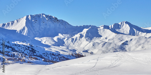 Panoramic view of the snowy high-altitude mountain range near the  Tignes ski resort in France during the winter season. #385019922