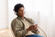 Attractive African American Guy In Headphones Enjoying Great Song, Listening To Audiobook Or Radio On Mobile Device