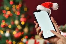 Hand Holding The Black Smartphone With Blank Screen And Santa Claus' Hat On Top On Christmas Background
