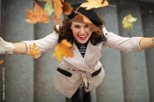 Fototapeta happy woman throwing autumn leaves obraz