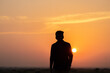 Silhouette of an Indian business man standing in front of the sun during the sunset