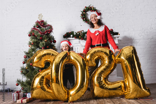 Obraz Daughter and mother in santa hats standing near balloons with numbers - fototapety do salonu