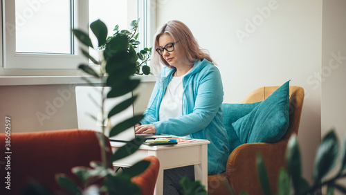 Fotografia Busy caucasian senior businesswoman with glasses is using a laptop at home while