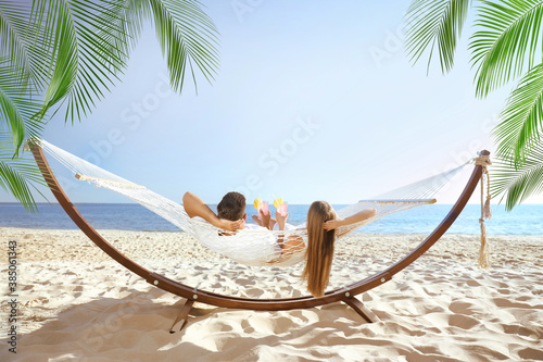 Obraz Couple with refreshing cocktails relaxing in hammock under green palm leaves on beach - fototapety do salonu