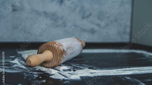 Obraz Wałek do ciasta z mąką na ciemnym czarnym tle do pieczenia - fototapety do salonu