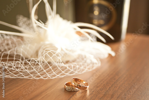 wedding rings symbol attributes lie on a table with hat or veil, glasses and bottles of champagne Canvas Print