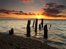 Remains Of The Old Wooden Jetty Looking Out Over The Sea To Harwich With A Stunning Sunset Of Clouds Lit Up In Orange, Felixstowe, Suffolk, UK
