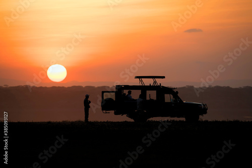 African safari car in red dawn sunrise with unknown silhouettes