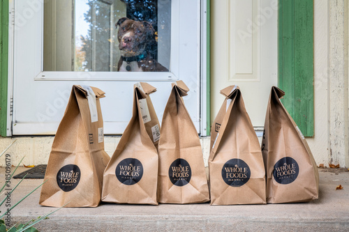 Brown bags with groceries and fresh produce delivered to house from Whole Food Market with a friendly pit bull dog in door. Online shopping during coronavirus pandemic.