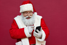 Happy Excited Old Bearded Santa Claus Wearing Costume Holding Cell Phone Using Mobile App On Smartphone Having Fun, Laughing, Isolated On Red Background. Christmas Promotion, Xmas Applications Ads.