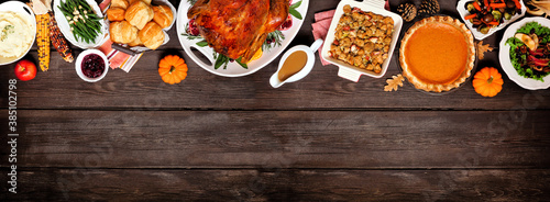 Fototapeta Traditional Thanksgiving turkey dinner. Above view top border on a dark wood banner background with copy space. Turkey, mashed potatoes, dressing, pumpkin pie and sides. obraz
