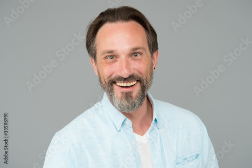 Obraz Happy mature man with healthy teeth and unshaven bearded face smile grey background, dental - fototapety do salonu